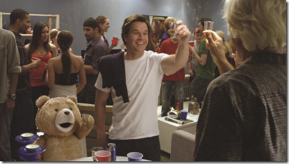 "John (MARK WAHLBERG) and his best friend, Ted (voiced by SETH MACFARLANE), do rum shots with the real Flash Gordon (SAM JONES) in the live action/CG-animated comedy ""Ted""."