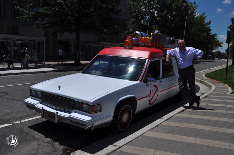 "A fan stands next to the new Ecto-1 from the upcoming film ""Ghostbusters"" outside of the Clarendon Metro in Arlington, VA"